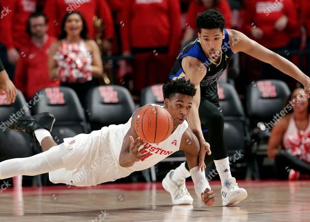 Houston guard Nate Hinton (11) falls as he passes the ball in front of Tulsa guard Zeke Moore (23) after recovering it on a scramble during the first half of an NCAA college basketball game, in Houston