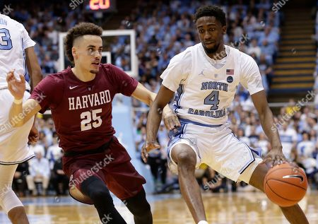 North Carolina's Brandon Robinson (4) dribbles while Harvard's Corey Johnson (25) defends during the first half of an NCAA college basketball game in Chapel Hill, N.C