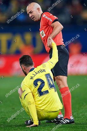 The referee helps Miguel Layun of Villarreal CF