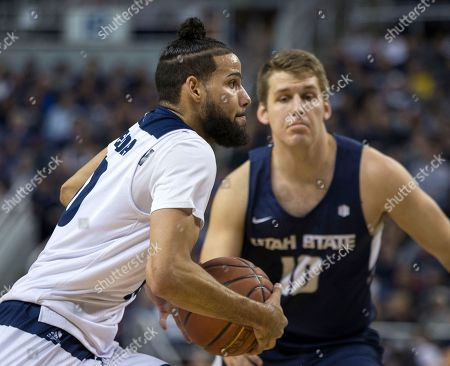 Stock Picture of Caleb Martin, Quinn Taylor. Nevada forward Caleb Martin drives past Utah State center Quinn Taylor (10) in the first half of an NCAA college basketball game in Reno, Nev