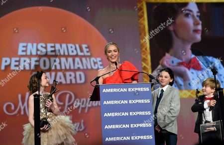 """Emily Blunt, Pixie Davies, Nathanael Saleh, Joel Dawson. Emily Blunt, center, from the cast of """"Mary Poppins Returns"""" accept the ensemble performance award at the 30th annual Palm Springs International Film Festival, in Palm Springs, Calif. Joining her on stage, from left, are cast members Pixie Davies, Nathanael Saleh and Joel Dawson"""