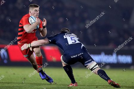 Owen Farrell of Saracens is tackled by James Phillips of Sale Sharks
