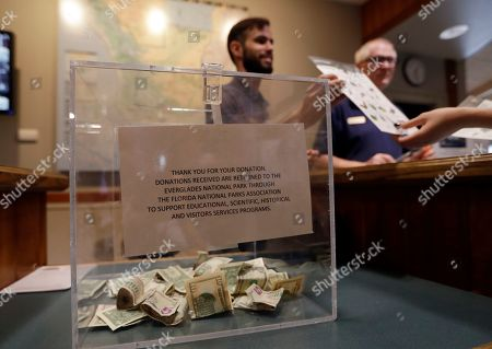 A donation box sits on the counter as Dany Garcia speaks with visitors at the Ernest F. Coe Visitor Center in Everglades National Park, in Homestead, Fla. Garcia is being paid by the Florida National Parks Association to work in the center during the partial government shutdown. As the shutdown drags, private organizations, local businesses, volunteers and state governments are putting up the money and manpower to keep national parks across the U.S. open, safe and clean for visitors