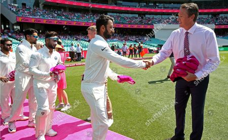 India's Cheteshwar Pujara, second right, presents to former Australian player Glenn McGrath, right, a pink cricket cap as support of McGrath's charity before play on day 3 of their cricket test match against Australia in Sydney