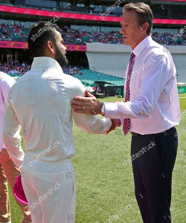India's captain Virhat Kohli, left, presents to former Australian player Glenn McGrath a pink cricket cap as support of McGrath's charity before play on day 3 of their cricket test match against Australia in Sydney