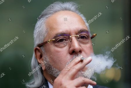 Stock Picture of Indian businessman Vijay Mallya takes a smoking break outside Westminster Magistrates Court in London. An Indian court has declared tycoon Vijay Mallya a fugitive economic offender, a ruling that empowers authorities to confiscate his properties and assets