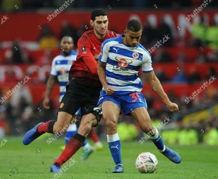 Stock Image of Reading's Andy Rinomhota, right, and Manchester United's Marouane Fellaini challenge for the ball during the English FA Cup third round soccer match between Manchester United and Reading at Old Trafford in Manchester, England
