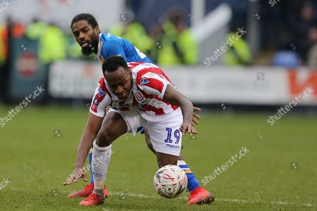 Stoke City forward Saido Berahino (19) and 42 Anthony Grant for Shrewsbury Town during the The FA Cup 3rd round match between Shrewsbury Town and Stoke City at Greenhous Meadow, Shrewsbury
