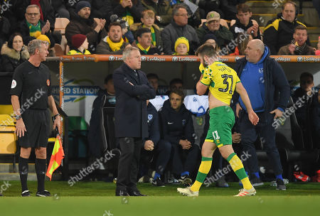 Grant Hanley of Norwich City reacts after being given a red card by Referee Darren Bond, Portsmouth Manager Kenny Jackett looks on