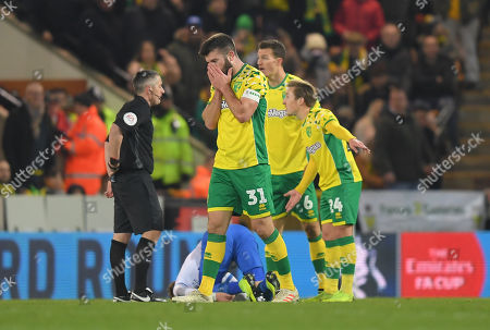 Grant Hanley of Norwich City reacts after being given a red card by Referee Darren Bond