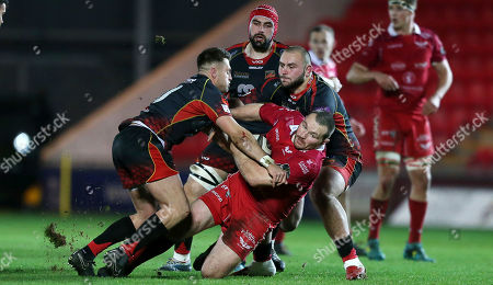 Ken Owens of Scarlets is tackled by Josh Lewis and Gerard Ellis of Dragons.