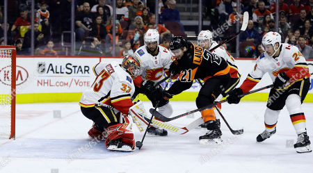 Scott Laughton, David Rittich. Philadelphia Flyers' Scott Laughton (21) cannot get the puck past Calgary Flames' David Rittich (33) as Oliver Kylington (58), Sam Bennett (93) and Travis Hamonic (24) defend during the second period of an NHL hockey game, in Philadelphia