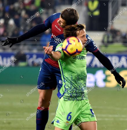 Huescas' defender Christian Rivera (L) in action against Betis' midfielder Sergio Canales during the Spanish LaLiga match between SD Eibar and Real Betis at El Alcoraz stadium in Huesca, Spain, 05 January 2019.