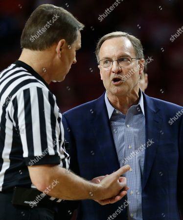 Oklahoma head coach Lon Kruger talks with an official in the first half of an NCAA college basketball game against Oklahoma State in Norman, Okla