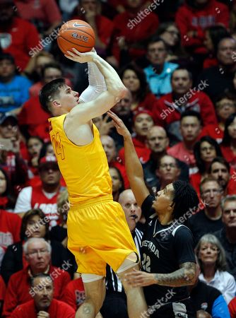 New Mexico guard Dane Kuiper, left, goes up for a basket against Nevada guard Jazz Johnson during the first half of an NCAA college basketball game in Albuquerque, N.M., . New Mexico won 85-58