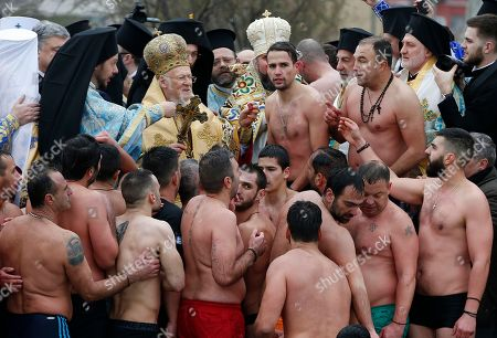 Ecumenical Patriarch Bartholomew I, center left, blesses men during the Epiphany ceremony in Istanbul, . The Ecumenical Patriarch of Constantinople on Sunday presented a decree of independence to the head of the nascent Orthodox Church of Ukraine, formally severing it from the Russian Orthodox Church