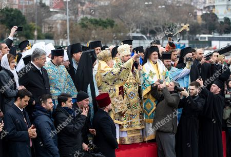 Greek Orthodox Ecumenical Patriarch Bartholomew I of Constantinople (C) throws a wooden cross into the cold waters of the Golden Horn while Metropolitan Epifaniy (6-R), the head of the united local Ukrainian Orthodox Church and  Ukrainian President Petro Poroshenko (L-2) attend the Epiphany Day ceremony in Istanbul, Turkey, 06 January 2019. Greek Orthodox swimmers take part in an annual race to retrieve a wooden crucifix thrown into the Bosphorus waters at the Golden Horn.