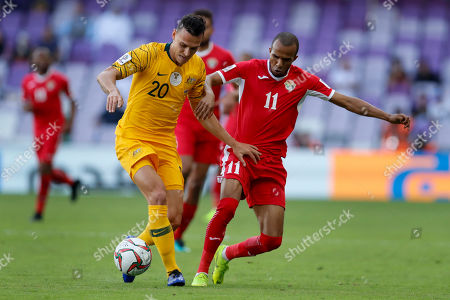Australia's defender Trent Sainsbury, left, battles for the ball with Jordan's midfielder Yasen Al-Bakhet during the AFC Asian Cup group B soccer match between Australia and Jordan at Hazza bin Zayed stadium in Al Ain, United Arab Emirates