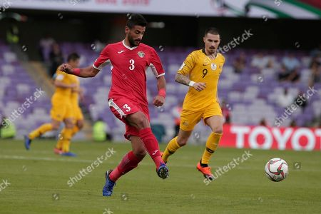 Jordan's defender Tareq Khattab, left, kicks the ball past Australia's forward Jamie Maclaren during the AFC Asian Cup group B soccer match between Australia and Jordan at the Hazza Bin Zayed stadium in Al Ain, United Arab Emirates
