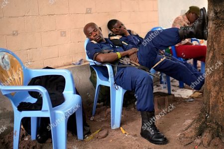 Congolese police officers rest as results are tallied for the presidential election at a local results compilation center in Kinshasa, Congo, . The winner of the Dec. 30 election will not be made public Sunday as expected, the head of the national electoral commission Corneille Nangaa told The Associated Press. The electoral commission will confirm the delay later Sunday