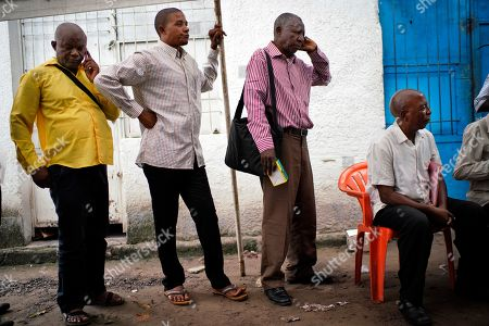 Congolese independent electoral commission (CENI) officials wait in line to be paid at a local results compilation center in Kinshasa, Congo, . The winner of the Dec. 30 election will not be made public Sunday as expected, the head of the national electoral commission Corneille Nangaa told The Associated Press. The electoral commission will confirm the delay later Sunday