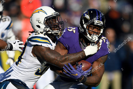 Week 13. Los Angeles Chargers defensive end Melvin Ingram, left, tackles Baltimore Ravens running back Gus Edwards in the first half of an NFL wild card playoff football game, in Baltimore