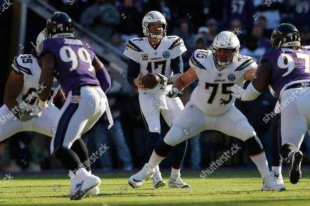 Los Angeles Chargers quarterback Philip Rivers (17) looks down field behind offensive tackle Sam Tevi (69) and offensive guard Michael Schofield (75) as Baltimore Ravens outside linebacker Matt Judon (99), defensive tackle Michael Pierce (97), move in during the first half of an NFL wild card playoff football game, in Baltimore