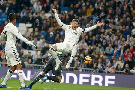 Real Madrid's Sergio Ramos jumps, with Real Sociedad's Asier Illarramendi, obscured behind, during a Spanish La Liga soccer match between Real Madrid and Real Sociedad at the Santiago Bernabeu stadium in Madrid, Spain