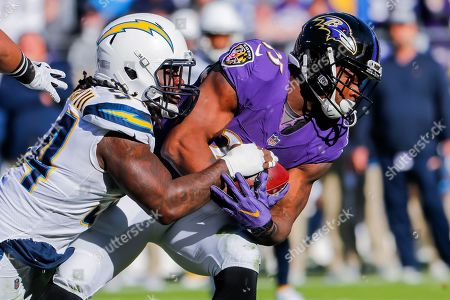 Baltimore Ravens running back Gus Edwards (R) is tackled by Los Angeles Chargers defensive end Melvin Ingram (L) during the first half of the NFL American football AFC wild card playoff game between the Los Angeles Chargers and the Baltimore Ravens at the M&T Bank Stadium in Baltimore, Maryland, USA, 06 January 2019.