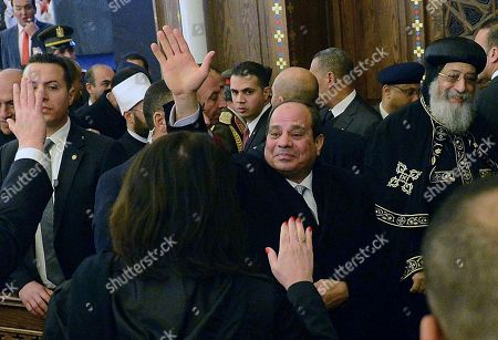 """Egyptian President Abdel-Fattah el-Sissi, center, greets Coptic Christians as he is accompanied by Coptic Pope Tawadros II, right, during Christmas Eve Mass at the new """"Cathedral of the Nativity of Christ,"""" in the new administrative capital, 40 kilometers (25 miles) east of Cairo, Egypt, late . Egypt's president is inaugurating a new cathedral for the Coptic Orthodox Church and one of the region's largest mosques in a highly symbolic gesture at a time when Islamic militants are increasingly targeting the country's minority Christians"""