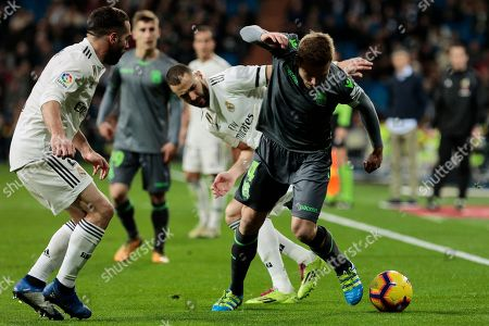 Stock Photo of Real Madrid's Dani Carvajal (L) and Karim Benzema (R) and Real Sociedad's Asier Illarramendi fight for the ball