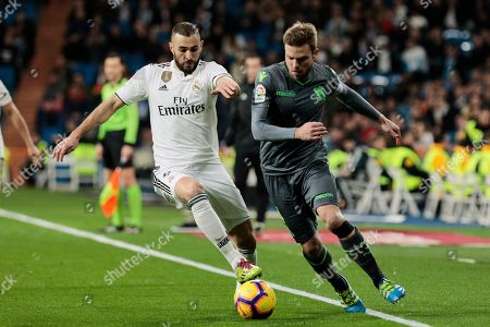 Real Madrid's Karim Benzema and Real Sociedad's Asier Illarramendi fight for the ball