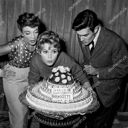 French actress Brigitte Bardot during her 22 years' party, with Micheline Presle and Louis Jourdan, on the set of the film 'La Mariee etait trop belle' (aka 'Her Bridal Night', or 'The Bride Is Much Too Beautiful'). FRANCE - 28/09/1956