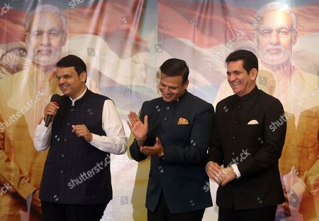 """Devendra Fadnavis, Vivek Oberoi, Umang Kumar. Maharashtra state Chief Minister Devendra Fadnavis, left, speaks with Bollywood actor Vivek Oberoi, center, and Director Omung Kumar standing beside him during the poster launch of the upcoming film """"PM Narendra Modi,"""" a biopic on the Indian Prime Minister, in Mumbai, India"""