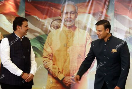 """Devendra Fadnavis, Vivek Oberoi. Maharashtra state Chief Minister Devendra Fadnavis, left, and Bollywood actor Vivek Oberoi stand for photographs in front of a poster of the upcoming film """"PM Narendra Modi,"""" a biopic on the Indian Prime Minister, during its poster launch in Mumbai, India"""