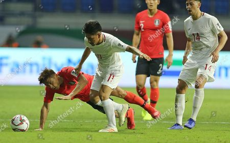 South Korea's midfielder Koo Ja-Cheol, left, is challenged by Philippines' defender Daisuke Sato during the AFC Asian Cup group C soccer match between South Korea and Philippines at Al Maktoum Stadium in Dubai, United Arab Emirates