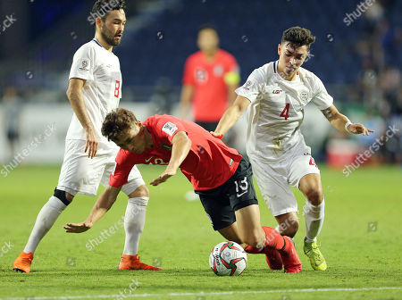 South Korea's midfielder Koo Ja-Cheol, center, is fouled by Philippines' midfielder John-Patrick Strauss during the AFC Asian Cup group C soccer match between South Korea and Philippines at Al Maktoum Stadium in Dubai, United Arab Emirates