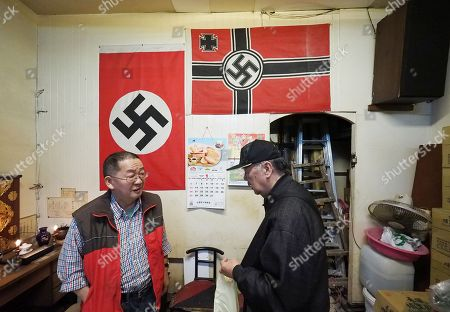Betel nut shop owner Mr Chen (L) talks to a friend (R) in his shop in Taipei, Taiwan, 07 January 2019. Chen recently has attracted media attention after an American photographer photographed the two Nazi swastica flags in Chen's shop and posted the photo on Instagram. The photographer asked Chen to remove the flags but Chen refused, saying he has displayed the flags for ten years as 'art' and no one had ever interfered. In recent years, a dozen incidents involving Nazi symbol have occurred in Taiwan, including a restaurant selling 'Long Live Nazi' spaghetti, a high school turning its Christmas celebration into a Nazi parade with students waving Nazi flags and shouting 'Heil Hitler' to the school principal, and 'Berlin Hair Salon' using the Nazi swastika to design its shop logo.