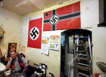 Betel nut shop owner Mr Chen poses for photograph in his shop in Taipei, Taiwan, 07 January 2019. Chen recently has attracted media attention after an American photographer photographed the two Nazi swastica flags in Chen's shop and posted the photo on Instagram. The photographer asked Chen to remove the flags but Chen refused, saying he has displayed the flags for ten years as 'art' and no one had ever interfered. In recent years, a dozen incidents involving Nazi symbol have occurred in Taiwan, including a restaurant selling 'Long Live Nazi' spaghetti, a high school turning its Christmas celebration into a Nazi parade with students waving Nazi flags and shouting 'Heil Hitler' to the school principal, and 'Berlin Hair Salon' using the Nazi swastika to design its shop logo.
