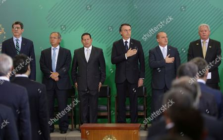 Jair Bolsonaro, Hamilton Mourao. Brazil's President Jair Bolsonaro, third from right, listens to Brazil's national anthem during a ceremony to present the new presidents of government banks at Planalto presidential palace in Brasilia, Brazil, . From left are National Bank for Social Development President Joaquim Levy, Economy Minister Paulo Gues, Vice President Hamilton Mourao, Presidente Jair Bolsonaro, Chief of Staff Onyx Lorenzoni and Bank of Brazil President Rubem Novaes