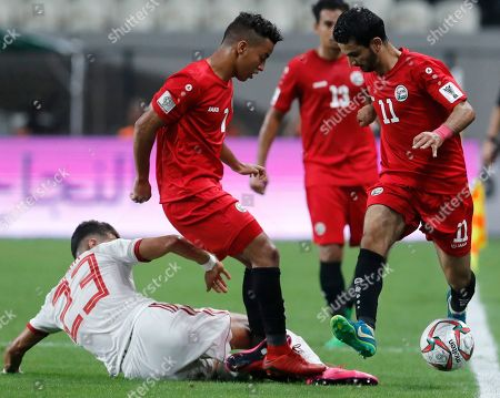 Iran's Ramin Rezaeian, left, Yemen's Abdulwasea Al-Matari, right, and Yemen's Ahmed Al-Sarori challenge for the ball during the AFC Asian Cup group D soccer match between Iran and Yemen at the Mohammed Bin Zayed Stadium in Abu Dhabi, United Arab Emirates