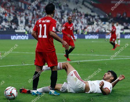 Iran's Mehdi Torabi reacts ahead of Yemen's Abdulwasea Al-Matari, left, during the AFC Asian Cup group D soccer match between Iran and Yemen at the Mohammed Bin Zayed Stadium in Abu Dhabi, United Arab Emirates