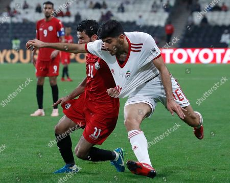 Yemen's Abdulwasea Al-Matari, left, and Iran's Mehdi Torabi challenge for the ball during the AFC Asian Cup group D soccer match between Iran and Yemen at the Mohammed Bin Zayed Stadium in Abu Dhabi, United Arab Emirates