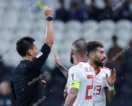 Referee Ryuji Sato, of Japan, gives yellow card to Iran's Ramin Rezaeian, right, during the AFC Asian Cup group D soccer match between Iran and Yemen at the Mohammed Bin Zayed Stadium in Abu Dhabi, United Arab Emirates