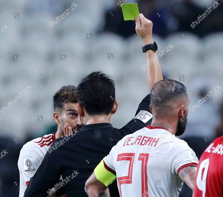 Referee Ryuji Sato, of Japan, gives yellow card to Iran's Ramin Rezaeian during the AFC Asian Cup group D soccer match between Iran and Yemen at the Mohammed Bin Zayed Stadium in Abu Dhabi, United Arab Emirates
