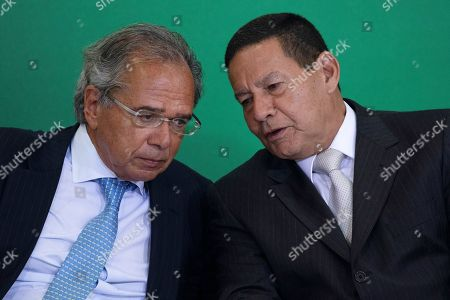 Stock Picture of Brazilian Economy Minister Paulo Guedes (L) and Vice-president, General Hamilton Mourao (R) talk during the possession ceremony of the presidents of the country's three main public banks, in Brasilia, Brazil, 07 January 2019. At the ceremony were presented the presidents of the Federal Economic Caixa, Pedro Guimaraes; Banco do Brasil, Rubem Novaes; and the National Bank for Economic and Social Development (BNDES), Joaquim Levy, all aligned with the liberal ideology of Economy Minister Paulo Guedes, an economist trained at the Chicago School.