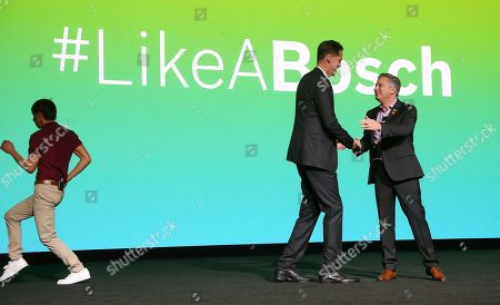 BOSCH Group management board member Markus Heyn, center, and president of BOSCH North America Mike Mansuetti, right, shake hands as Shawn Ryan, left, an actor in the latest BOSCH advertising campaign, runs off stage at the BOSCH new conference at CES International, in Las Vegas