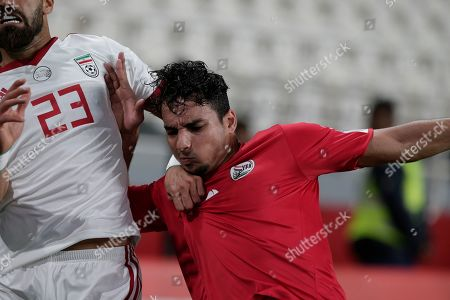 Iran's defender Ramin Rezaeian, left, fights for the ball with Yemen's defender Alaaddin Mahdi during the AFC Asian Cup group D soccer match between Iran and Yemen at the Mohammed Bin Zayed Stadium in Abu Dhabi, United Arab Emirates