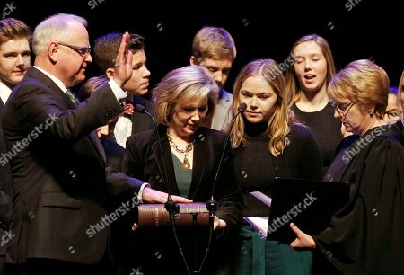 Stock Photo of Tim Walz, Lorie Skjerven Gildea. Minnesota Governor-elect Tim Walz, left, places his hand on the Bible held by his wife Gwen, center, as he prepares to take the oath of office administered by Supreme Court Chief Justice Lorie Skjerven Gildea, right, in St. Paul, Minn