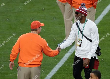 Clemson head coach Dabo Swinney talks to Terrell Owens before the NCAA college football playoff championship game against Alabama, in Santa Clara, Calif